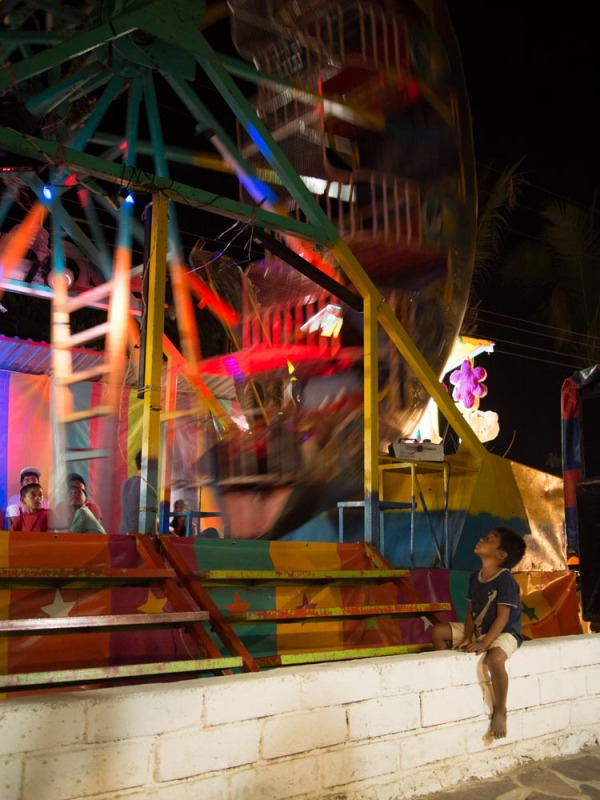 A young boy watches as children big enough ride the swinging ship.
